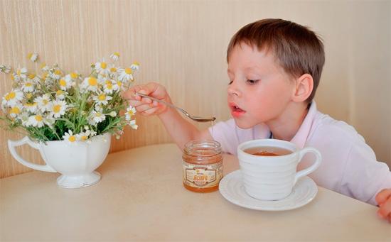 Ребенок пьёт чай с медом