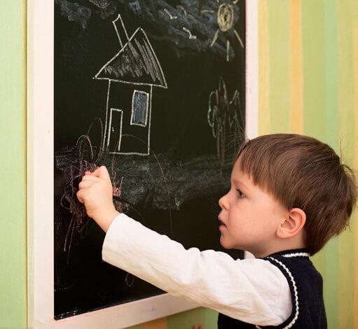 Ребенок рисует на доске мелом