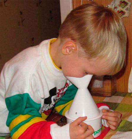 Мальчик делает паровую ингаляцию
