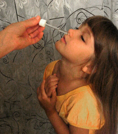 Девочке закапывают в нос физраствор