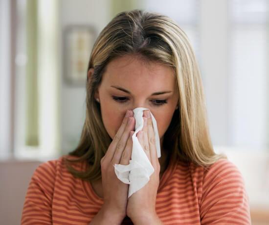 Вытирающая платком нос девушка