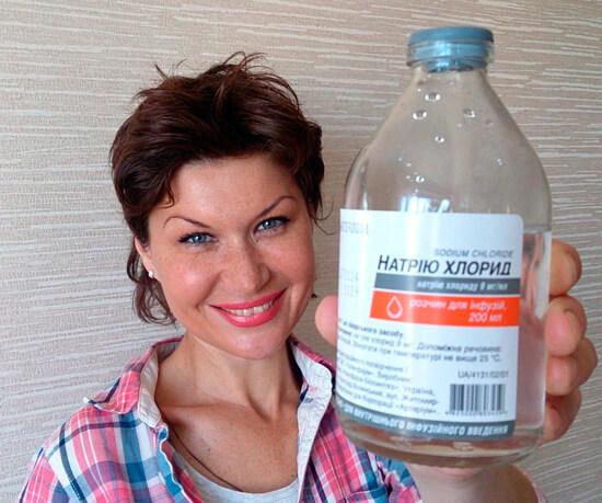 Девушка демонстрирует бутылку с физраствором