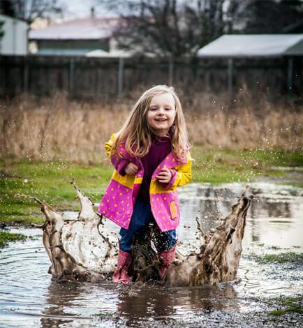 Не стоит запрещать ребенку играть в лужах или под мелким дождём - вреда ему это не причинит.