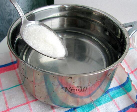 Ложка соли и кастрюля с водой