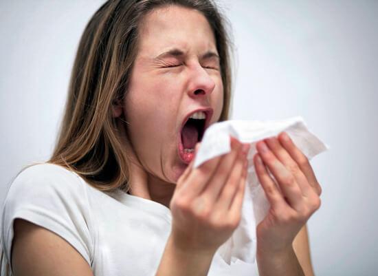Девушка с насморком чихает