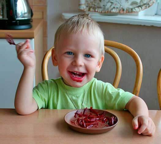 Мальчик ест свеклу